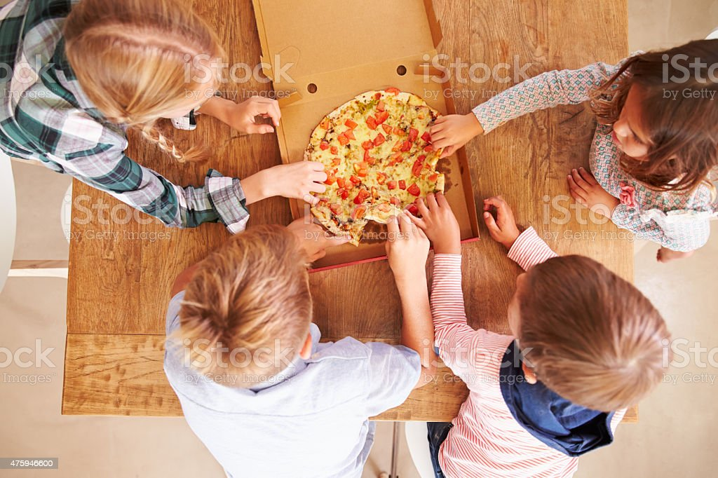 Children sharing a pizza together, overhead view stock photo