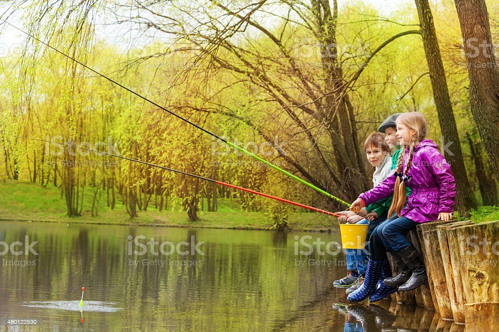 Children sitting and fishing together near pond stock photo