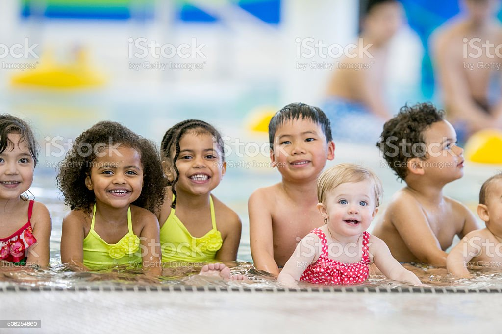 Children Sitting in a Shallow Pool stock photo