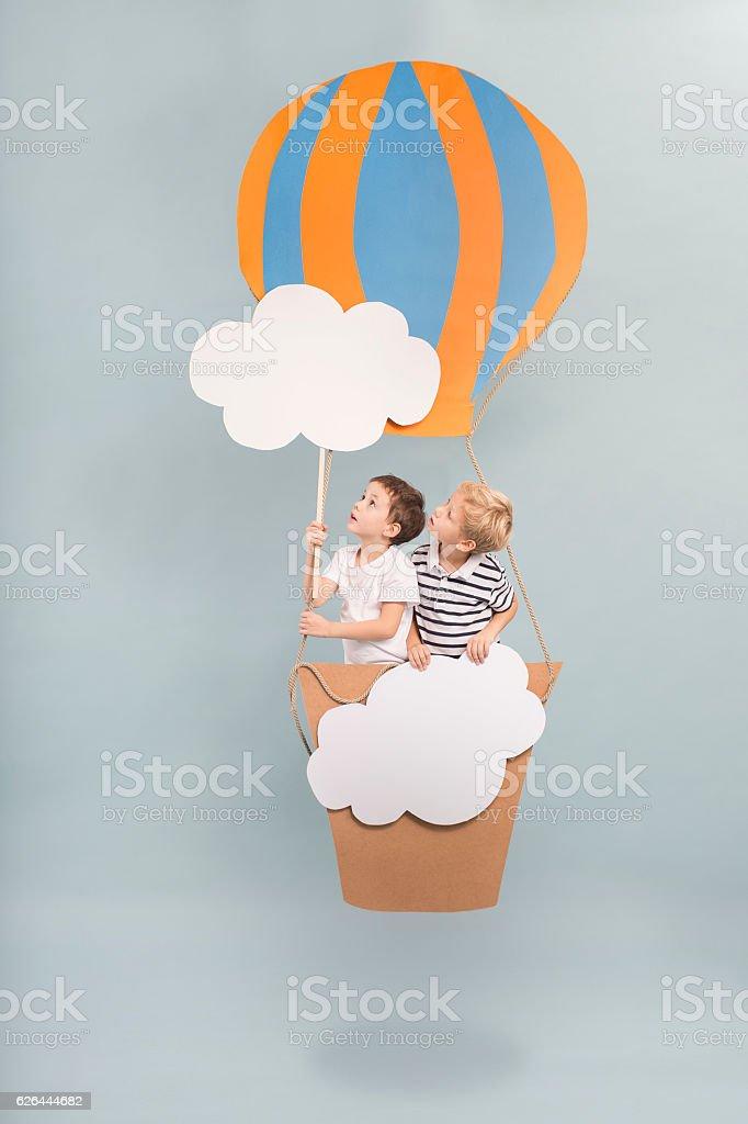 Children sitting in balloon basket stock photo