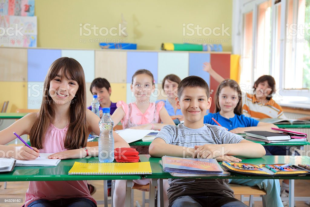 Children sitting in classroom. stock photo