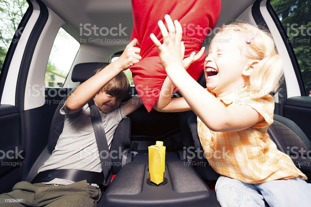 children sitting in the car, having a pillow fight stock photo