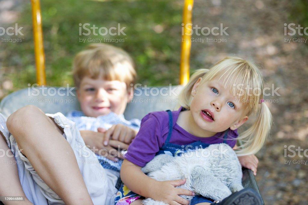 Children sitting in wheelbarrow stock photo
