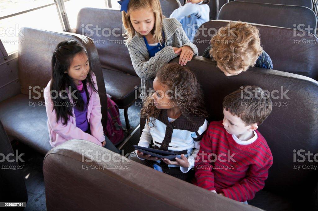 Children sitting inside school bus with digital tablet stock photo