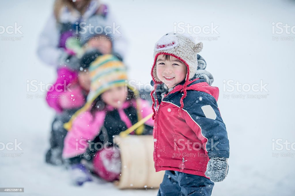 Children Sitting on a Sled on a Winter Day stock photo