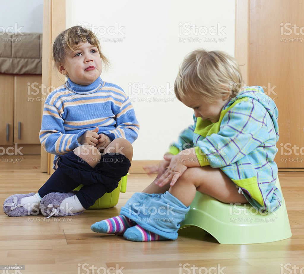 children sitting on bedpans stock photo