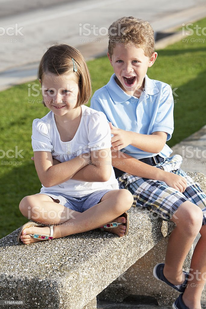 Children sitting on bench outdoors stock photo