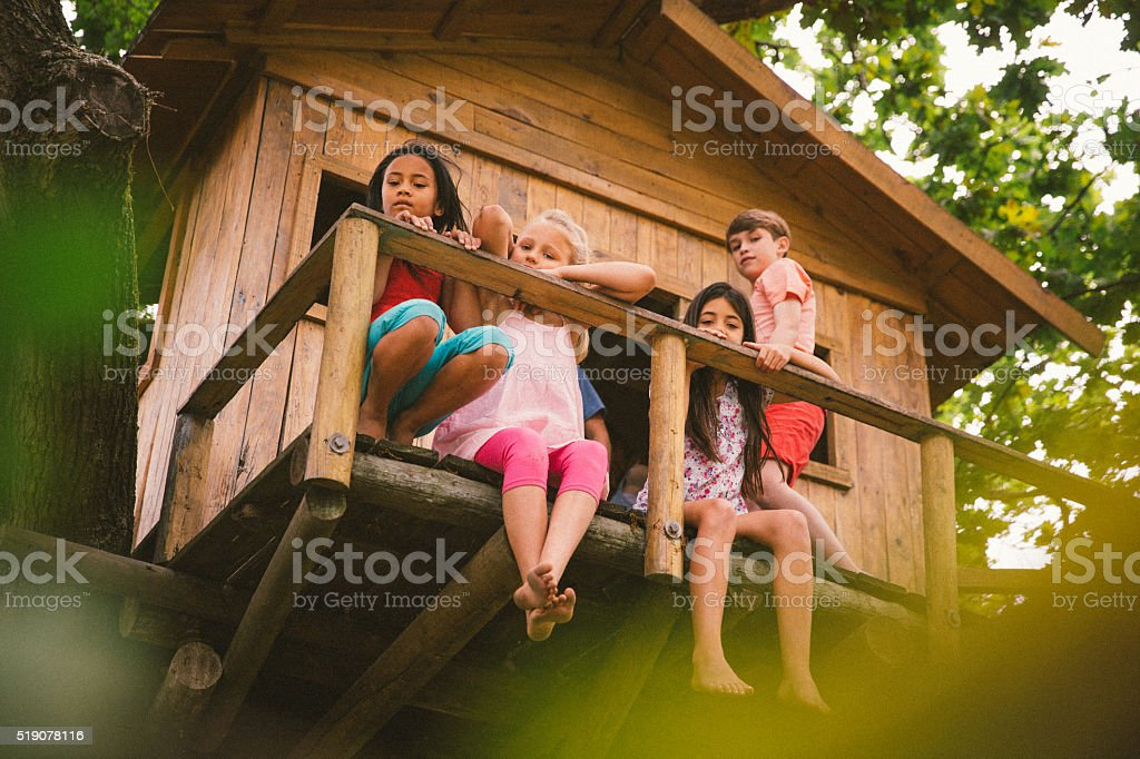 Children sitting on edge of a rustic wooden treehouse stock photo