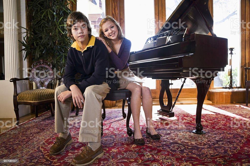 Niños, sentado en el banco de piano foto de stock libre de derechos