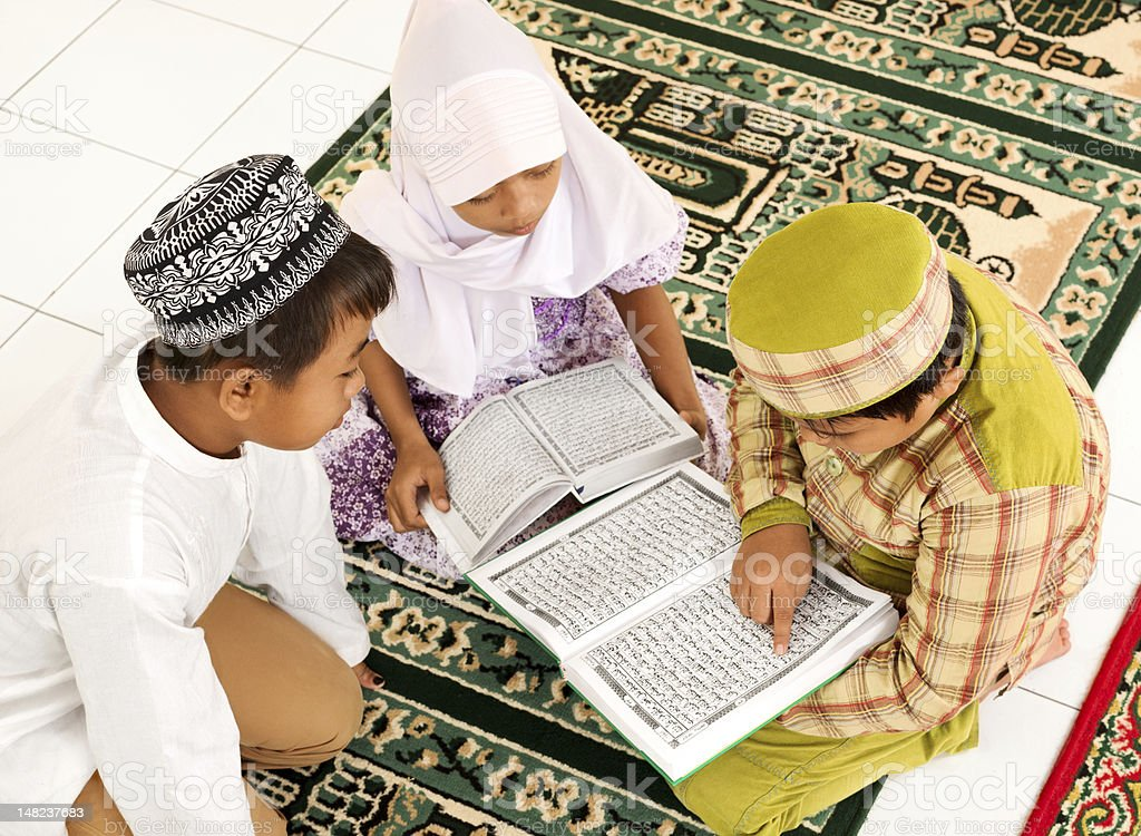 Children sitting on the floor reading the Quran stock photo