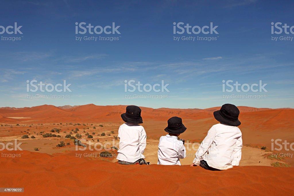 Children Sitting on Top of Red Sand Dunes Sossusvlei Namibia stock photo