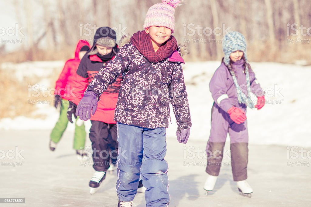 Children Skating on a Frozen Pond stock photo