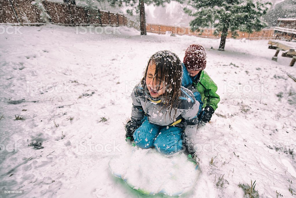 Children sled backwards in a large snow storm stock photo