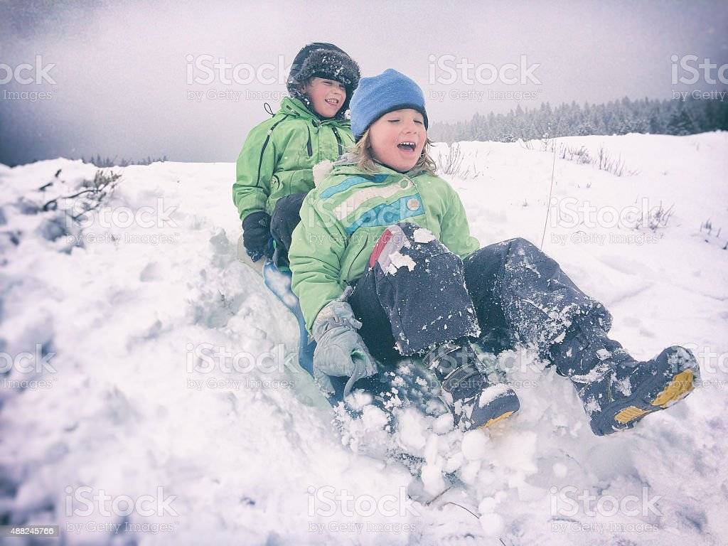 Children sledding together in snowy weather stock photo