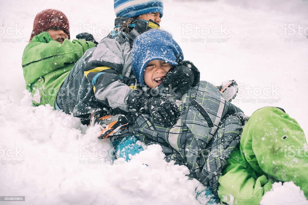 Children sledding together laughing during a storm stock photo