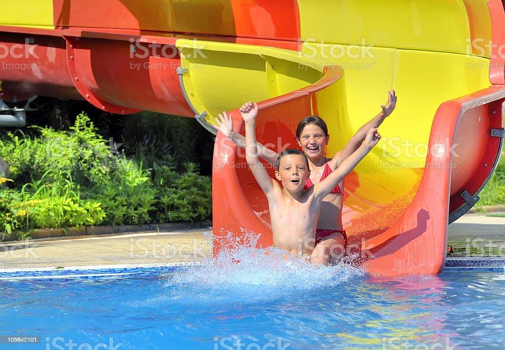 children sliding down a water slide stock photo
