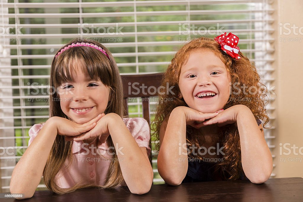 Children:  Smiling friends sit happily with their hands folded. royalty-free stock photo