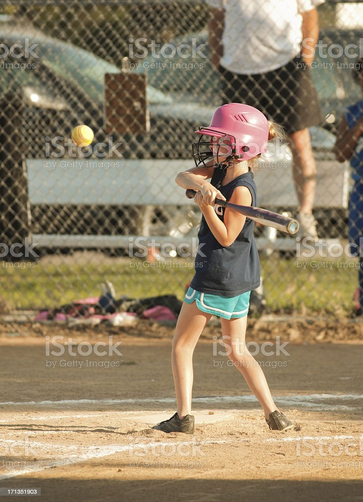 A young girl batting the softball in softball tournament game.