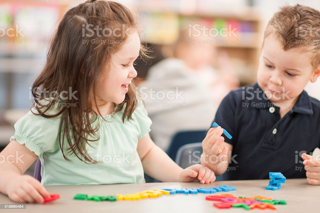 Children Spelling with Plastic Letters stock photo