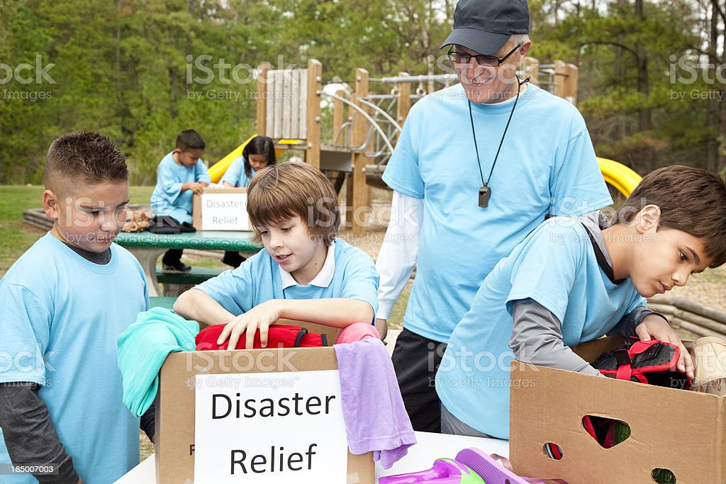 Children sports team collecting donations for disaster relief victims. Volunteers. stock photo