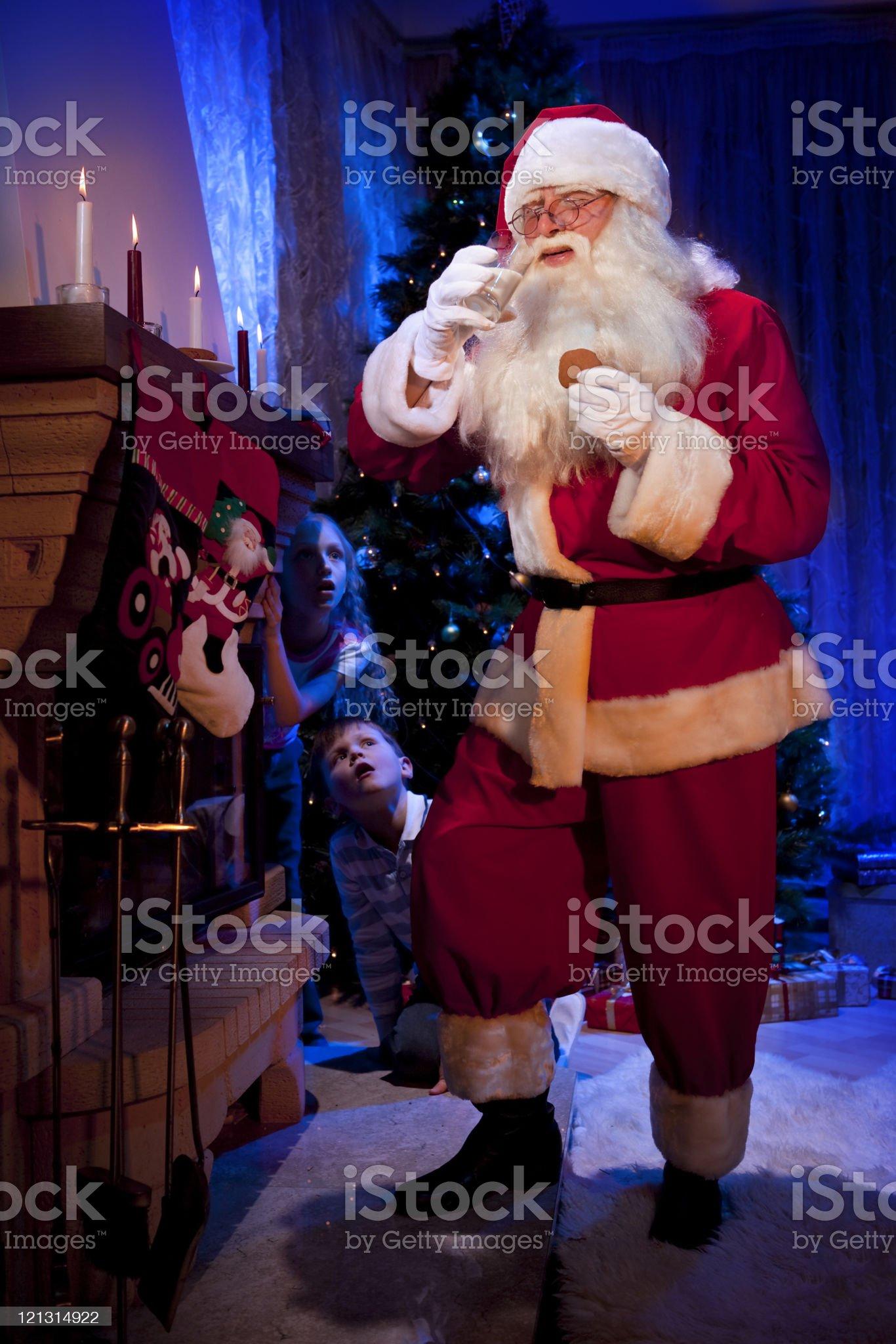 Children spying how Santa drinking milk. royalty-free stock photo