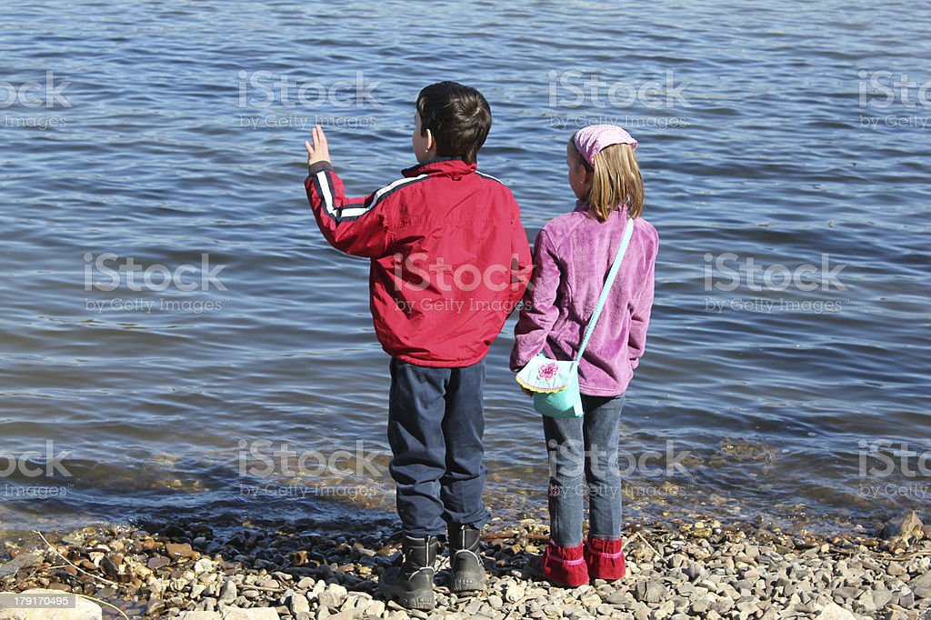 Children standing and playing at the lake royalty-free stock photo