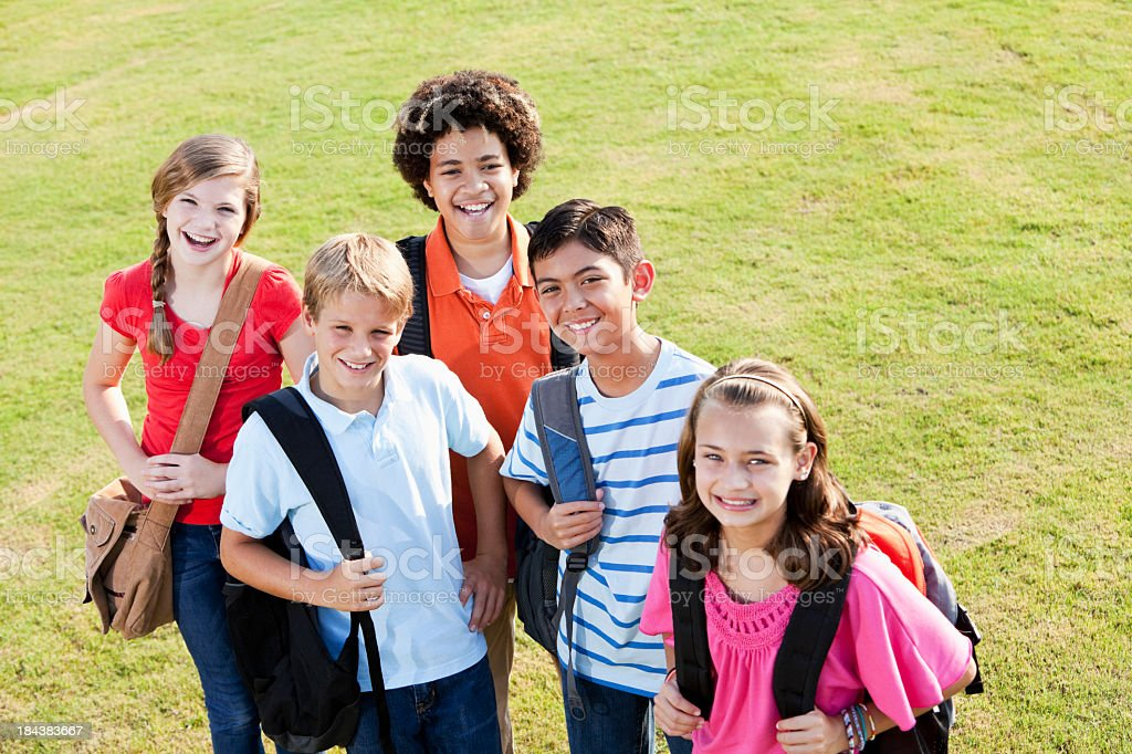 Children standing outside school with bookbags stock photo