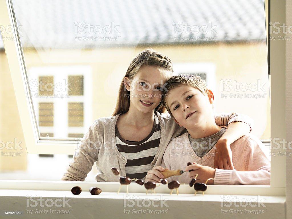 Children standing together in window stock photo
