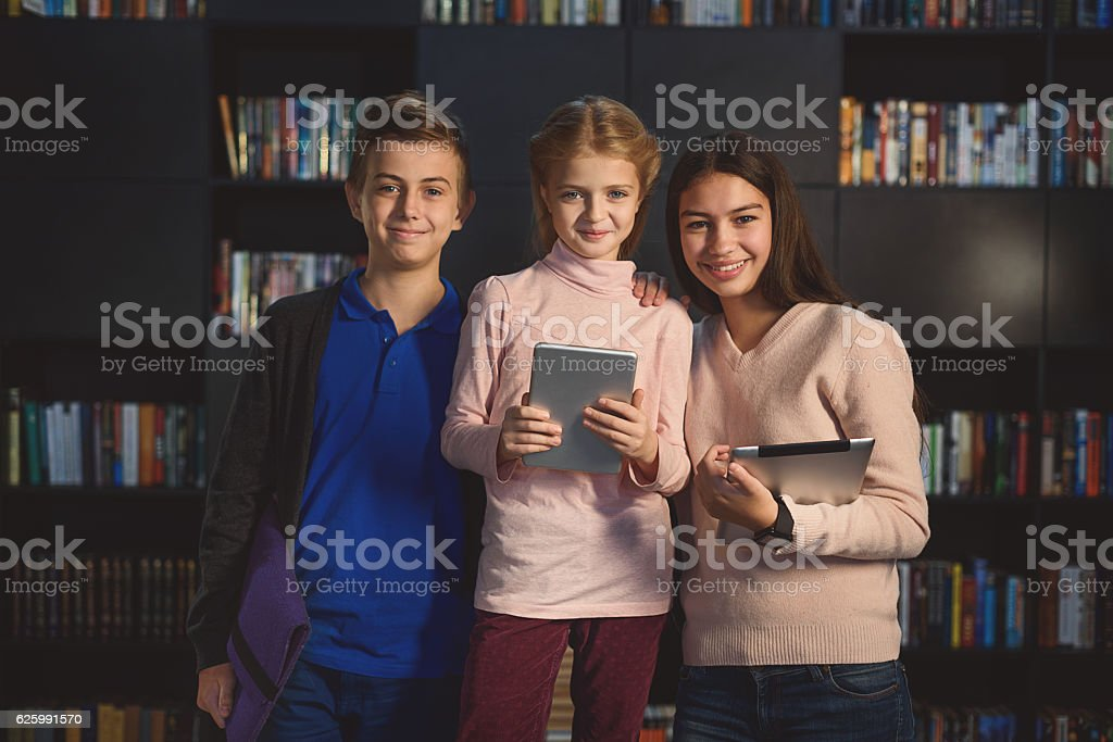 Children staying and smiling with tabs stock photo
