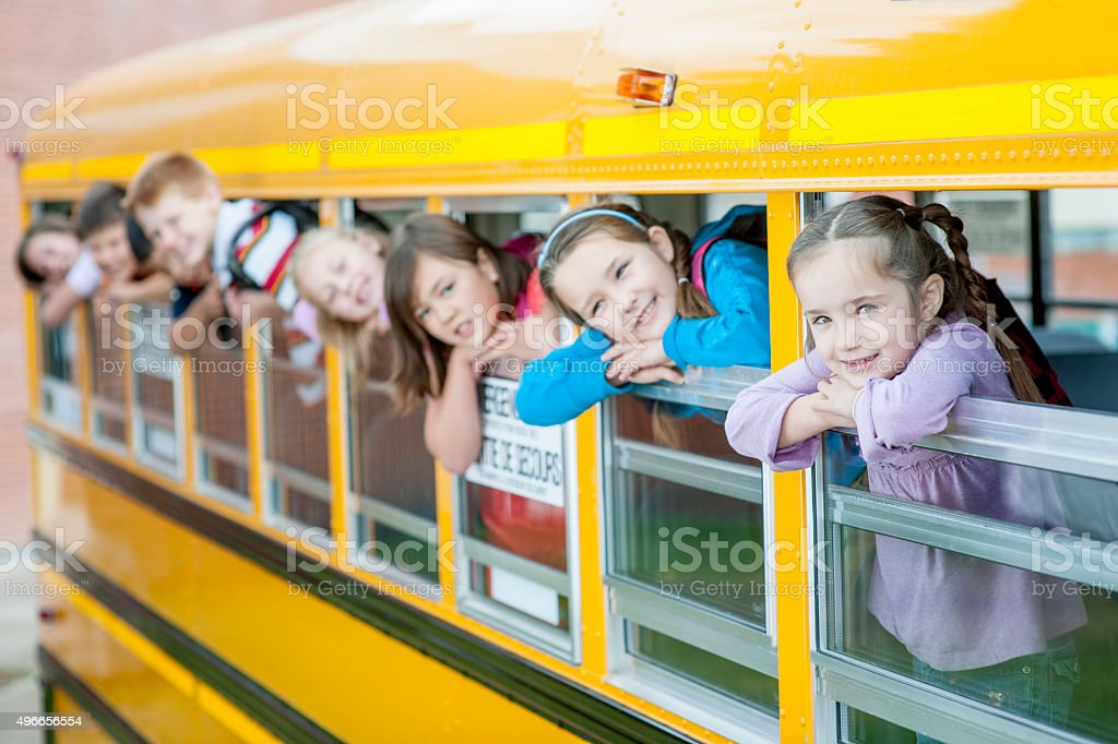 Children Sticking Their Heads Out of the School Bus stock photo