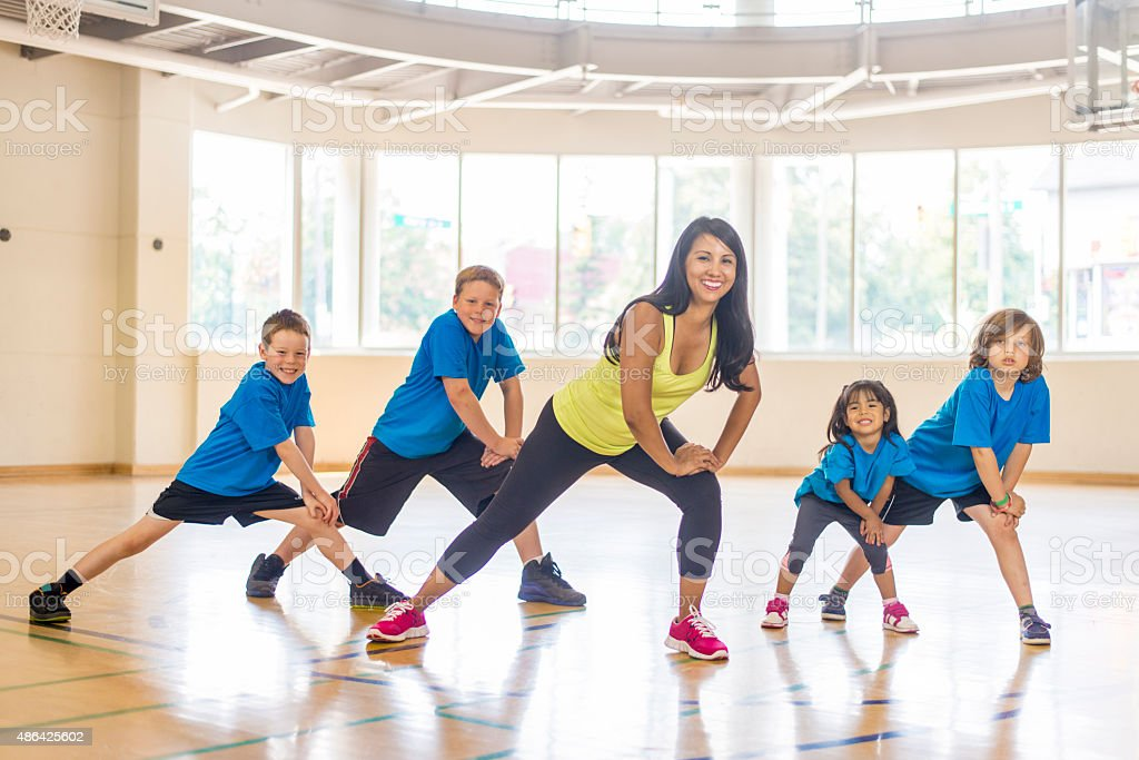 Children Stretching Their Legs in Gym Class stock photo