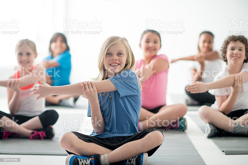 Children Stretching Together in PE Class stock photo