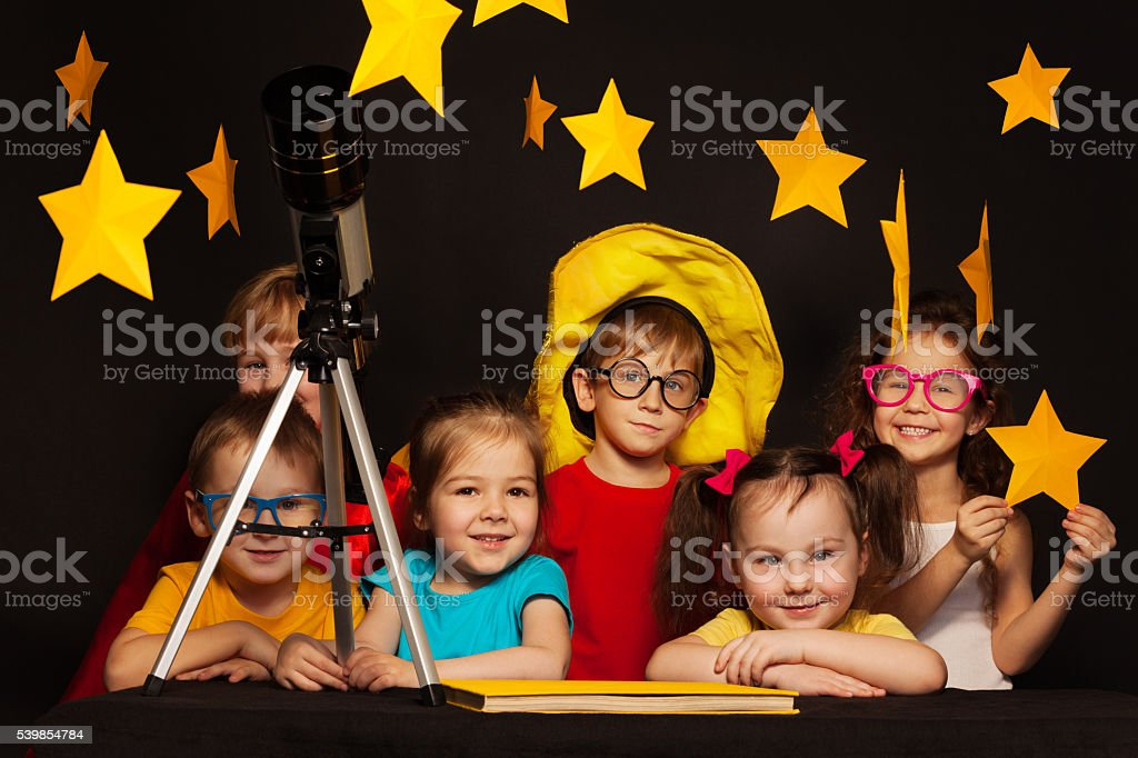 Children studying astronomy with telescope stock photo