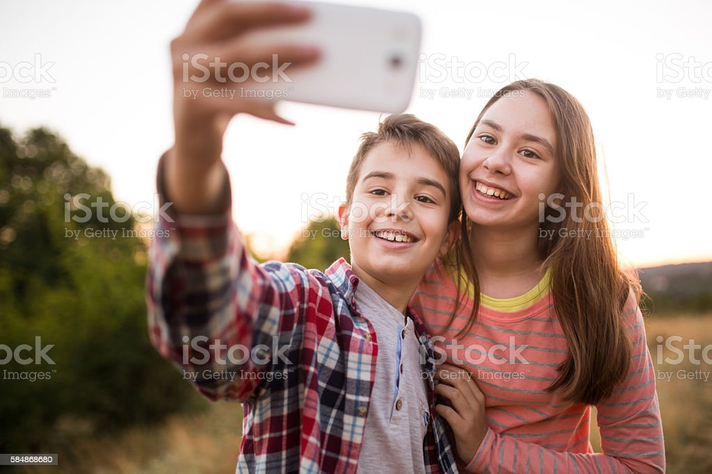 Children take selfie with a smart phone in nature stock photo
