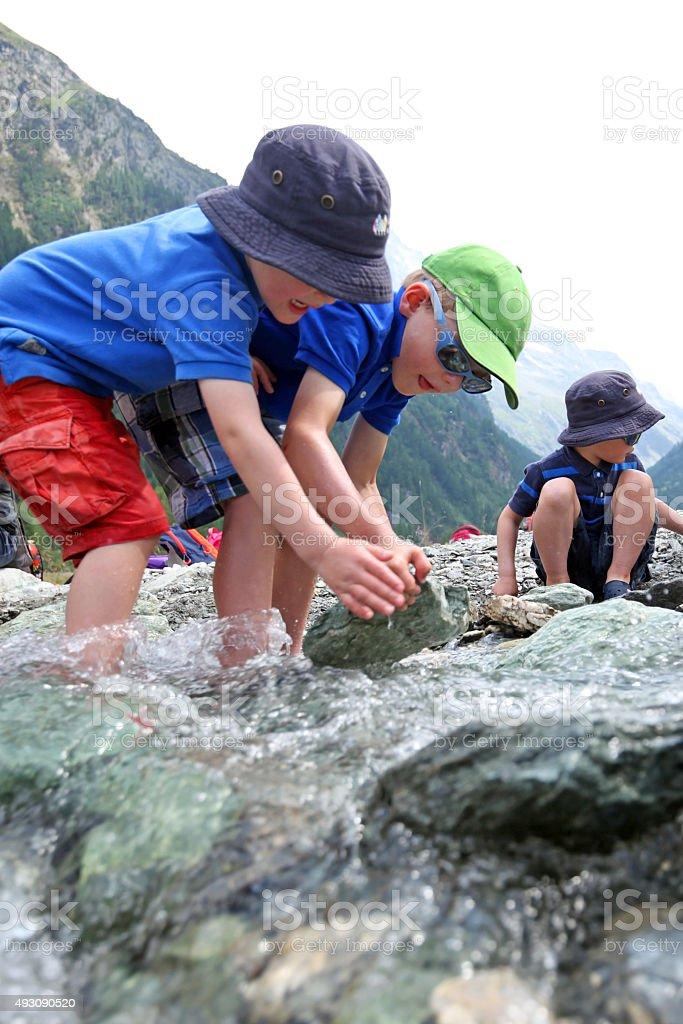Children Teamwork Building a River Dam Together stock photo