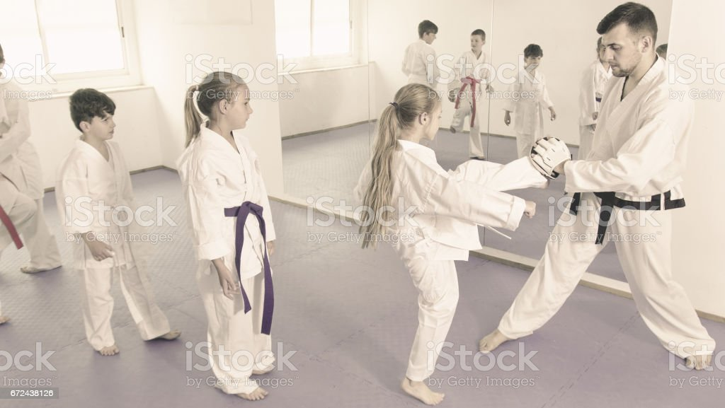 Children training karate kicks on punching bag during karate class stock photo