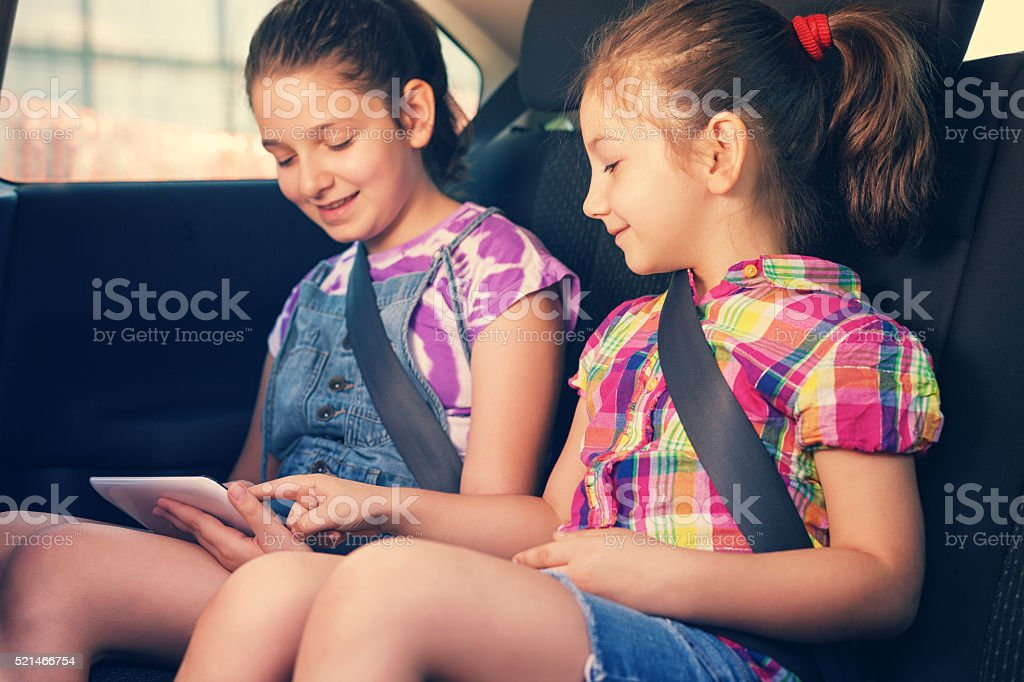 Children Travelling in Car With Tablet stock photo