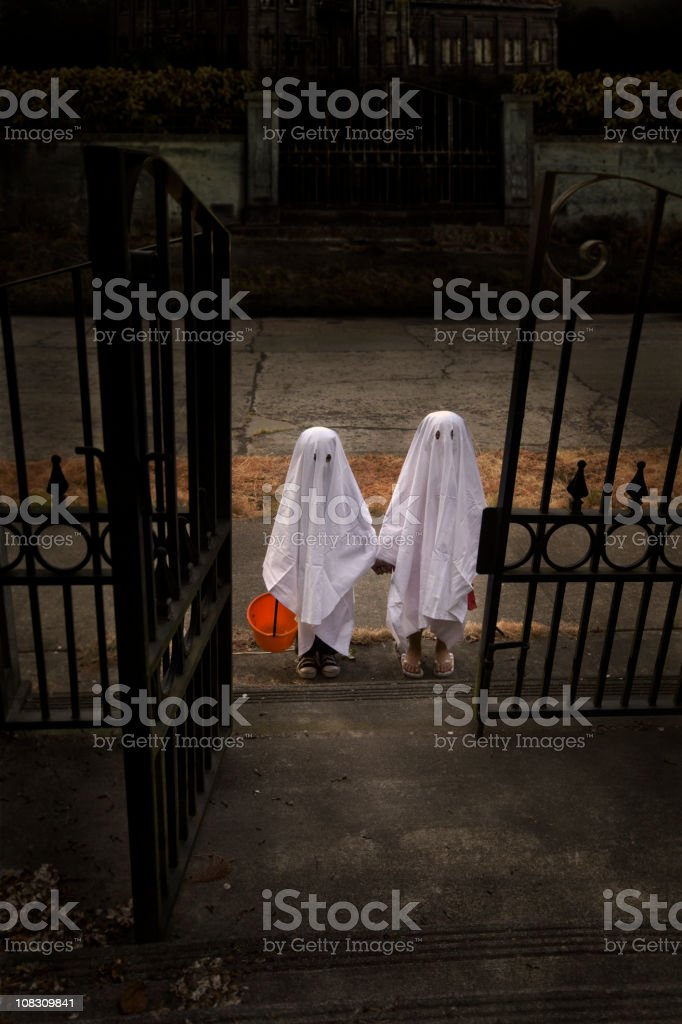 Children Trick or Treat in Ghost Costumes at Haunted House stock photo