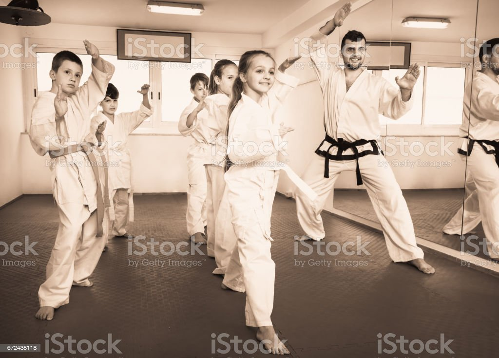 Children trying martial moves in karate class stock photo