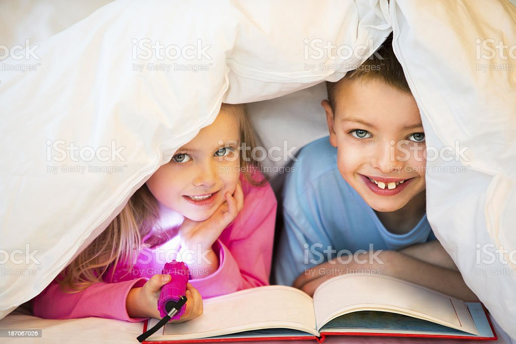 Children Under Bed Covers stock photo