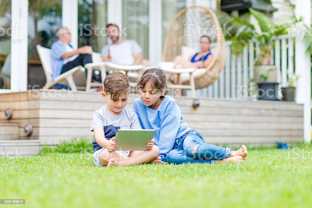 Children using a digital tablet on the grass stock photo