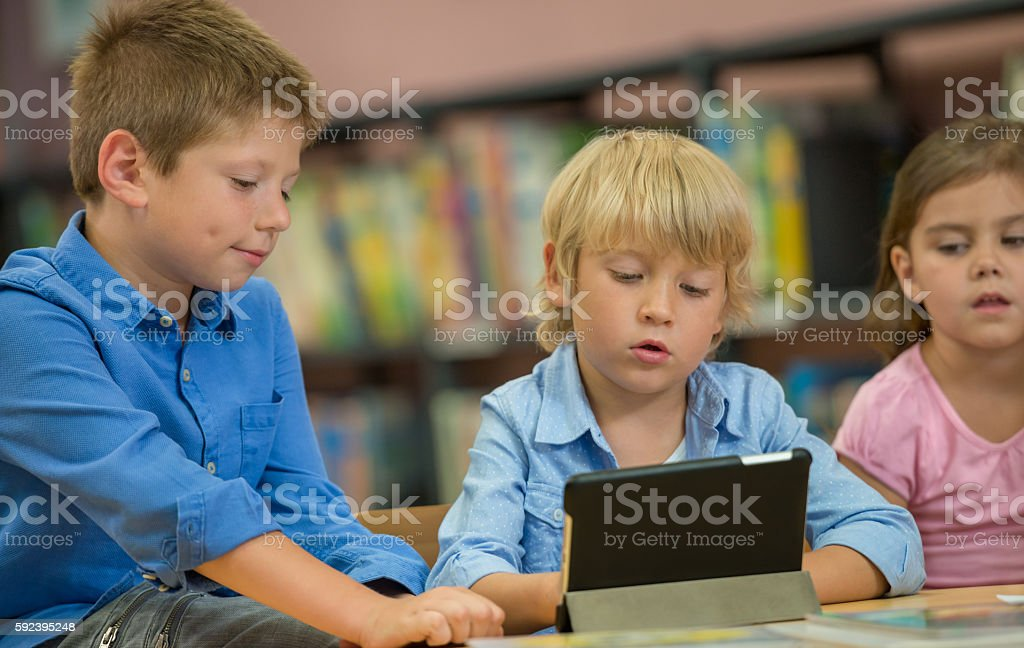 Children Using Digital Tablet In Public Library stock photo