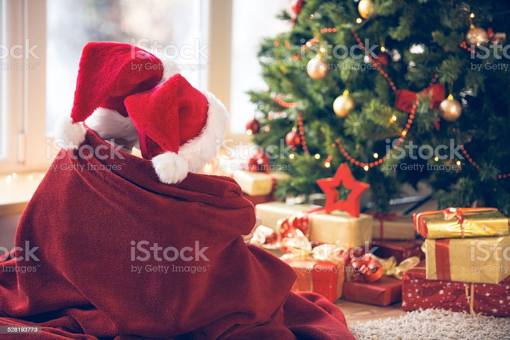 Children waiting for Christmas by the tree stock photo