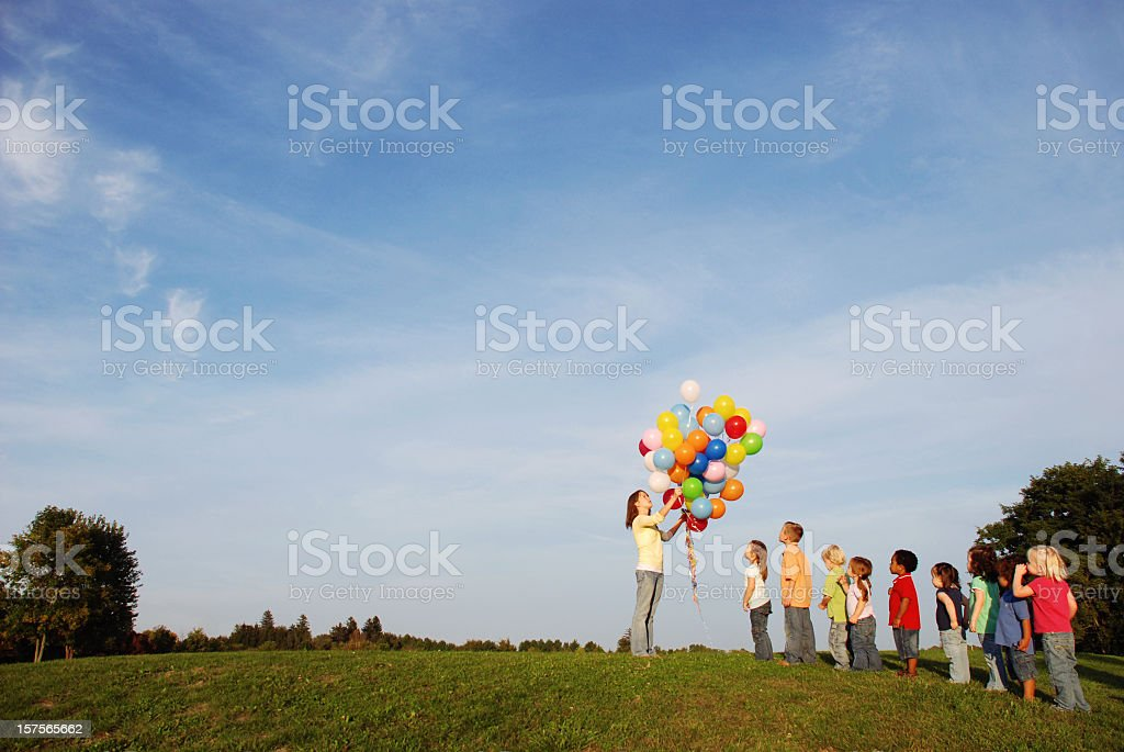 Children Waiting in Line for Balloons Outside royalty-free stock photo