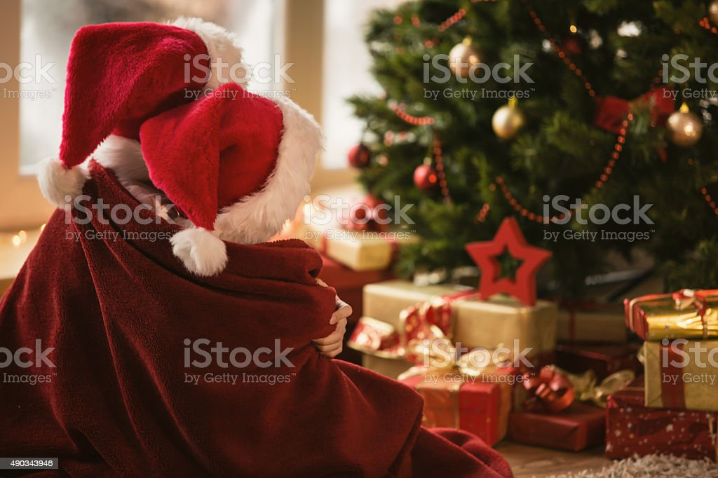 Children waiting Santa by the Christmas tree stock photo