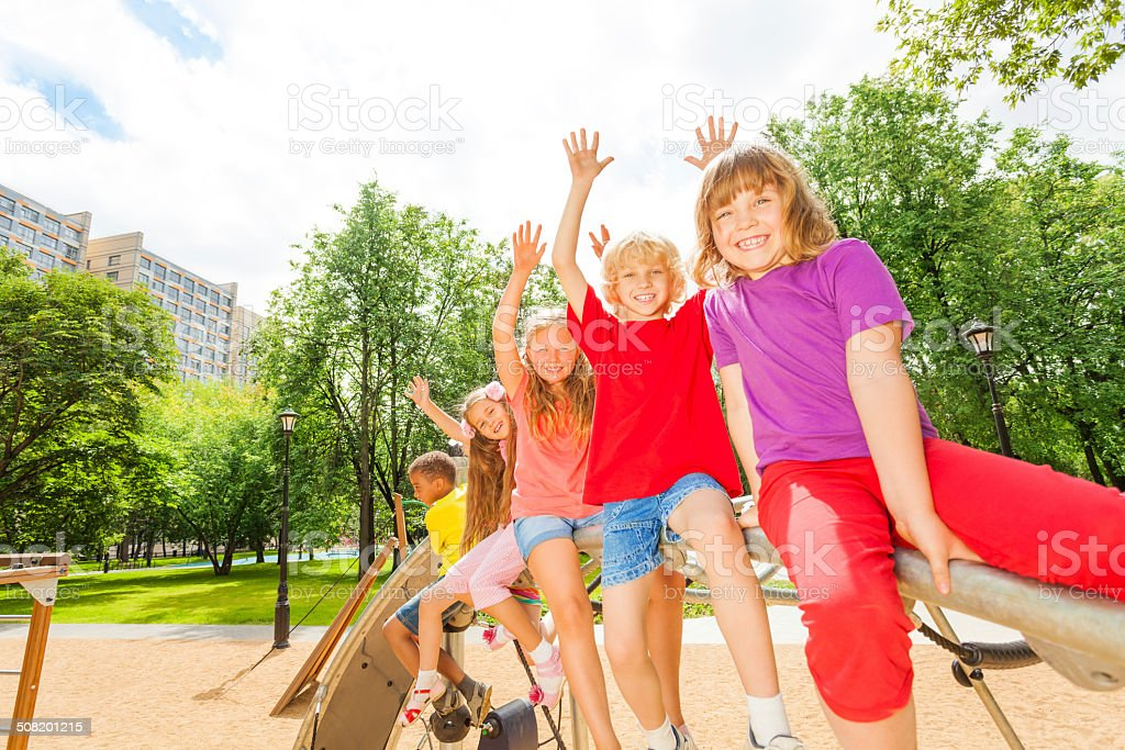 Children waive hands sitting in row on round bar stock photo