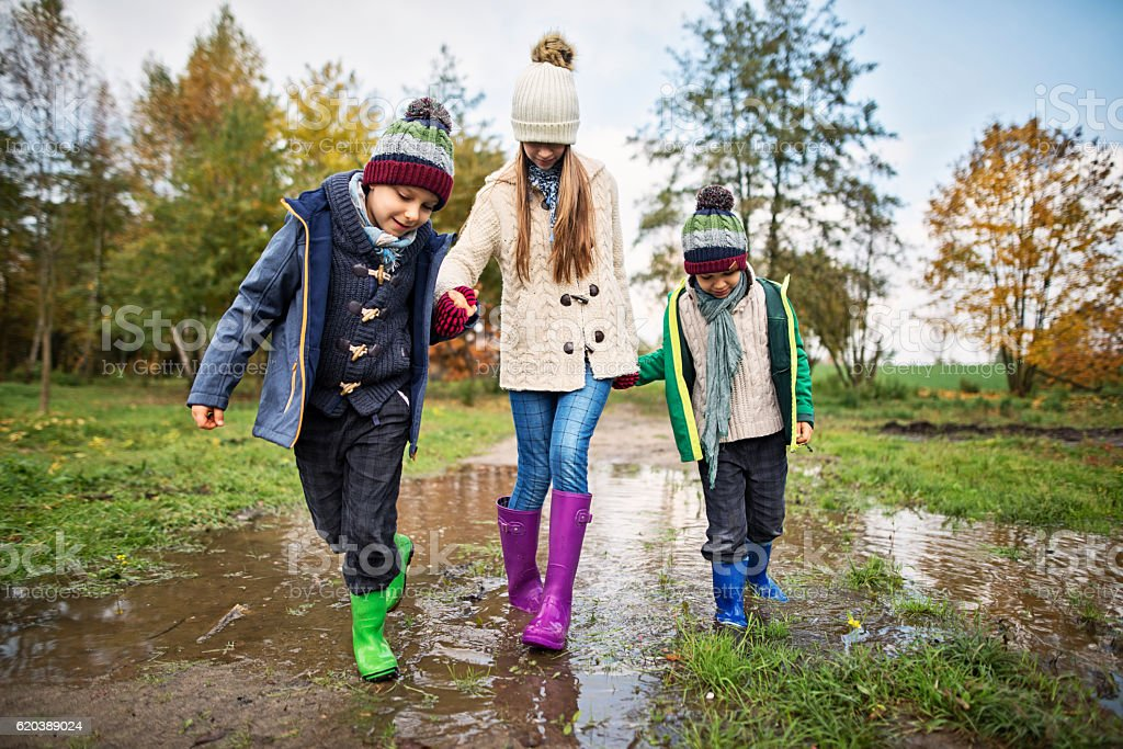 Children walking in a puddle in autumn stock photo