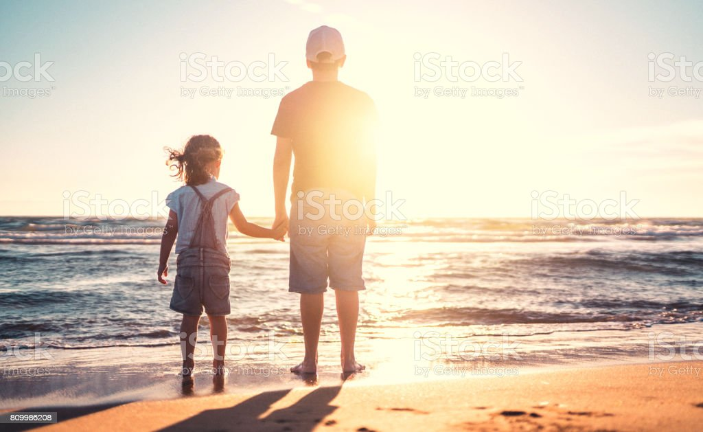 Children walking on the beach at sunset stock photo