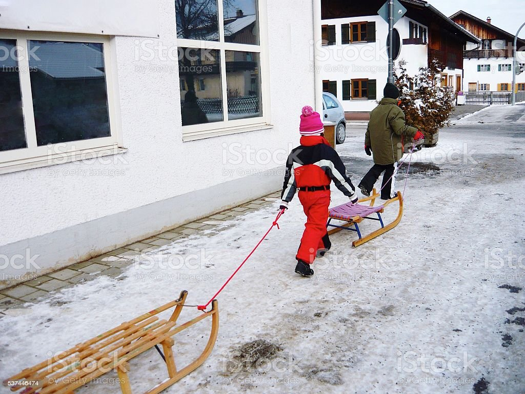 Children walking through an German town with sleds stock photo