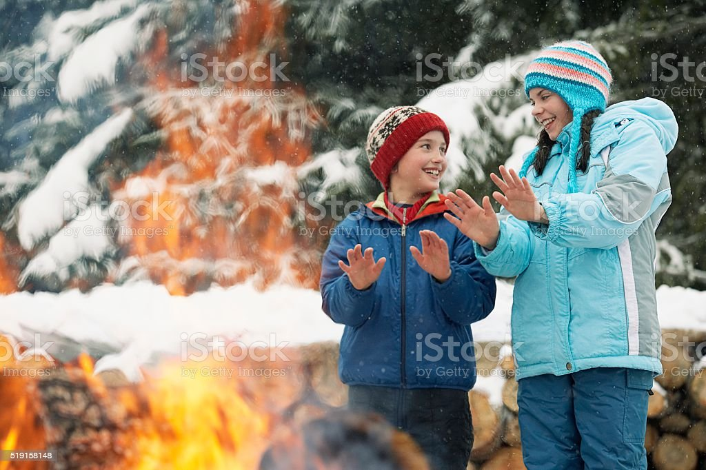 Children warming hands by a fire stock photo